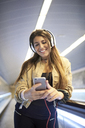 Portrait of smiling young woman with headphones standing on escalator looking at cell phone - JNDF00020