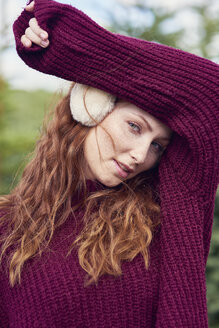 Portrait of redheaded young woman wearing ear muff and knit pullover - ABIF00698