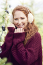 Portrait of happy redheaded young woman wearing ear muff and knit pullover - ABIF00701