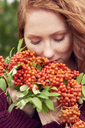 Portrait of freckled redheaded young woman with rowanberries - ABIF00713