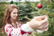 Redheaded young woman decorating Christmas tree outdoors - ABIF00716