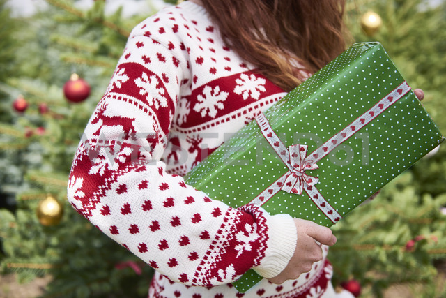 Woman holding Christmas present, partial view - ABIF00719