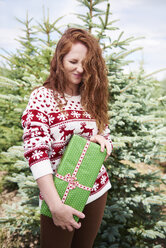 Redheaded young woman with Christmas present outdoors - ABIF00722