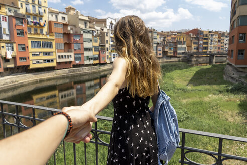 Spain, Girona, woman holding man's hand exploring in the city - AFVF00807