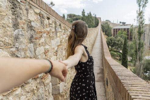 Spain, Girona, woman holding man's hand walking along stone wall - AFVF00810
