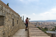 Spain, Girona, man at the castletaking picture of the city - AFVF00813