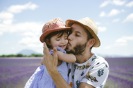 France, Provence, Valensole plateau, father kissing daughter in lavender fields in the summer - GEMF02127