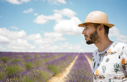 France, Provence, Valensole plateau, man wearing straw hat in lavender fields in the summer - GEMF02157