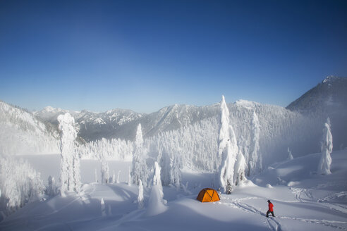 Michael Hanson walks through deep powder to his campsite in the snow covered Cascade Mountains overlooking Snow Lake. - MINF00126