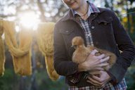 A woman holding a small brown fluffy chicken. A long brown knitted scarf on a washing line. Autumn sunshine filtering through trees. - MINF00138