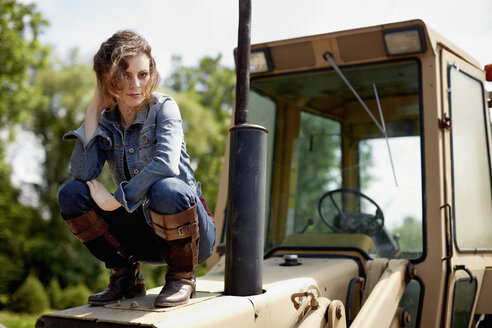 A young woman in denim jacket and boots on the hood of a tractor. - MINF00195