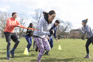 People racing, doing team building exercise in sunny park - CAIF21191