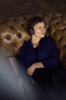 Woman with headphone lying on sofa, listening music - RBF06441