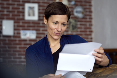 Woman reading letter at home - RBF06447