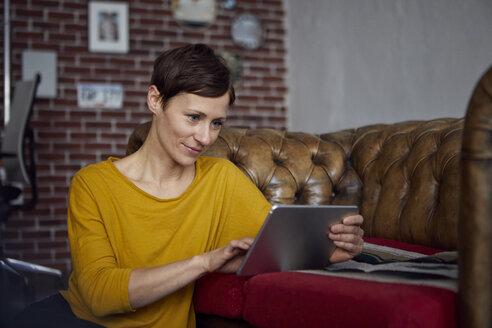 Woamn sitting at home, using digital tablet - RBF06450