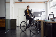Businesswoman with bicycle in her start-up company - RBF06453