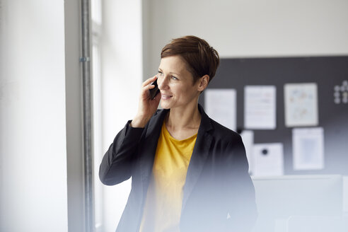 Attractive businesswoman standing in office, using smartphone - RBF06462