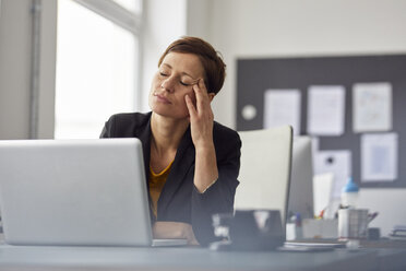 Businesswoman sitting in office, having a headache - RBF06465