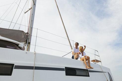 Mature couple making holidays, sailing on a catamaran - EBSF02574