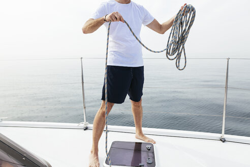 Mature man standing on catamaran, coiling rope - EBSF02580