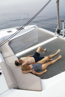 Mature couple on a sailing trip lying on trampoline, relaxing - EBSF02583