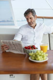 Mature man on a sailing trip having a healthy breakfast, reading newspaper - EBSF02589