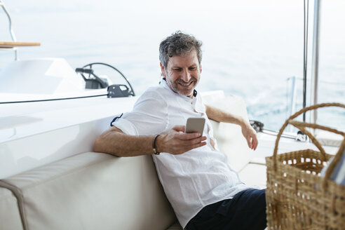 Mature man on a sailing trip having, using smartphone - EBSF02592