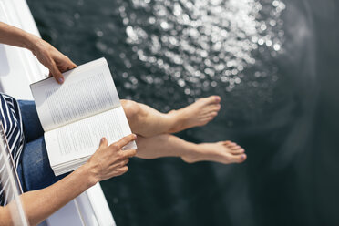 Woman sitting on sailing boat, reading a book - EBSF02595