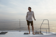 Marure man on catamaran, looking ta view - EBSF02604