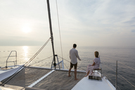Mature couple standing on catamaran trampoline, enjoying their sailing trip - EBSF02610