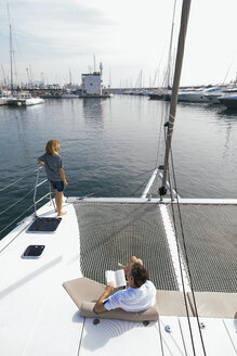 Couple on a catamaran, man sitting and reading book - EBSF02613