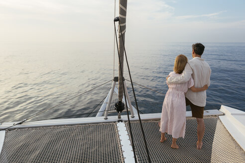 Mature couple standing on catamaran trampoline, enjoying their sailing trip - EBSF02619