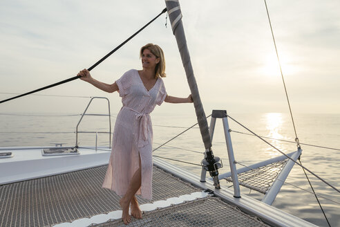 Mature woman on catamaran, watching sunset - EBSF02625