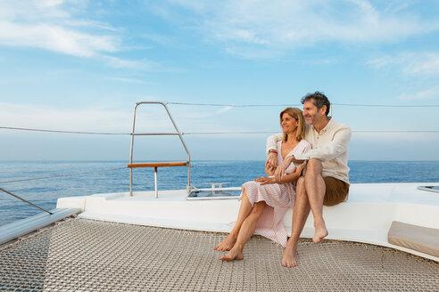 Mature couple enjoying quality time on sailing trip on a catamaran - EBSF02628