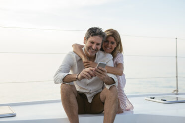 Mature couple looking at smartphone, sitting on a sailing boat - EBSF02631