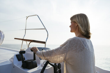 Mature woman navigating catamaran on a sailing trip - EBSF02637