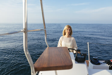 Mature woman navigating catamaran on a sailing trip - EBSF02640