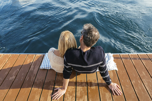 Mature couple sitting on jetty, relaxing at the sea - EBSF02646