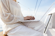 Woman sitting on catamaran, using laptop - EBSF02649