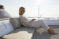 Woman sitting on catamaran, using laptop - EBSF02652