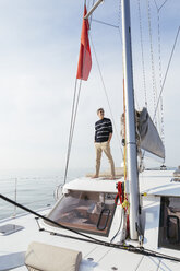 Mature man standing on a catamaran with hands in pockets, smiling - EBSF02658