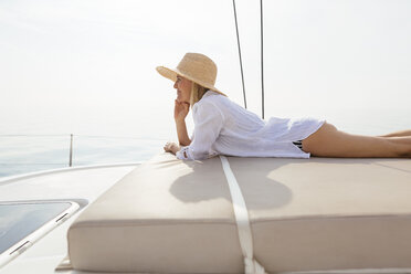 Mature woman relaxing on a catamaran, taking a sunbath - EBSF02661