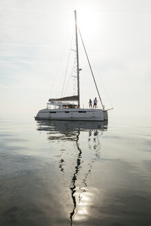 Couple setting off for a sailing trip on a catamaran - EBSF02664