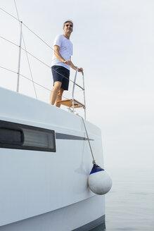 Marure man on catamaran, looking ta view - EBSF02670
