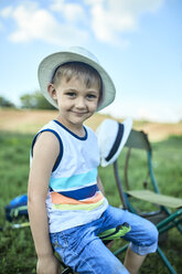 Portrait of smiling little boy wearing summer hat - ZEDF01473
