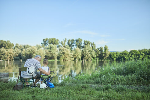 Back view of grandfather and grandson fishing together at lakeshore - ZEDF01479