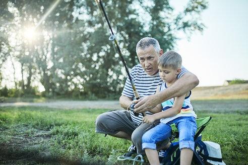 Grandfather and grandson fishing together at lakeshore - ZEDF01482