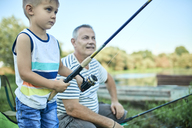 Little boy fishing together with his grandfather at lakeshore - ZEDF01485