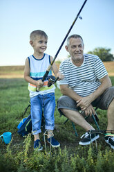 Grandfather and grandson fishing together at lakeshore - ZEDF01488
