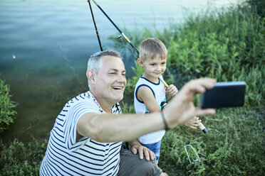 Grandfather and grandson taking selfie with smartphone at lakeshore - ZEDF01491